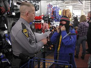 State Highway Patrolman Bob Ashenfelter helps Austyn Curley, 10, of Bowling Green, choose a stocking cap.