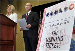 Arizona Lottery Director of Budget, Products and Communications Karen Bach, left, and Arizona Lottery Executive Director Jeff Hatch-Miller stand next to an enlargement of the winning $587.5 Million Powerball ticket.