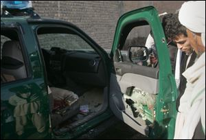 Afghans look at a damaged police vehicle after it was hit by a roadside bomb in Herat, west of Kabul, today.