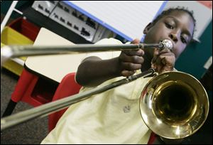 A student tests his trombone at the Toledo School for the Arts. The school, which enrolls about 580 students, typically has a waiting list of about 100, school director Martin Porter said. Under the expansion, the school plans to accept up to 60 more students in grades nine through 12.