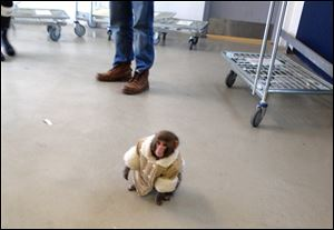 A small monkey wearing a winter coat and a diaper wanders around at an IKEA in Toronto Sunday.