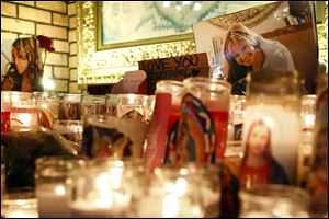 Candles and pictures are displayed to pay tribute to singer Jenni Rivera at the Plaza Mexico shopping center in Lynwood, Calif., early today.