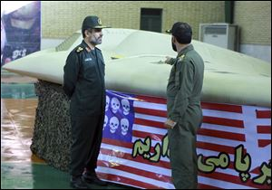 A photo released in December, 2011, by the Iranian Revolutionary Guards, purports to show the chief of the aerospace division of Iran's Revolutionary Guards, Gen. Amir Ali Hajizadeh, left, listening to an unidentified colonel pointing to a U.S. RQ-170 Sentinel drone which Tehran says its forces downed.