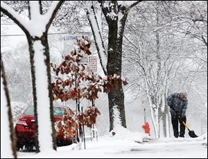 Jean Bohlinger shovels snow from the sidewalk in front of his daughter's house, Sunday, in Winona, Minn.