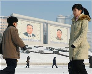 North Koreans walk by the portraits of they country's national founder Kim Il Sung, left, and late leader Kim Jong Il in Pyongyang, North Korea today.
