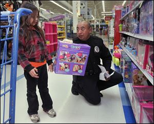 Cygnet, Ohio, resident Brooklyn McKee, 7, shops with Owens Community College police officer Luis Munguia during a shopping spree at Meijer in Rossford, Ohio.