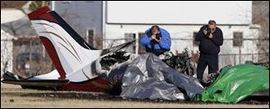 Investigators photograph a plane crash at Munson Park Tuesday, 3/30/11, in Monroe, Michigan.