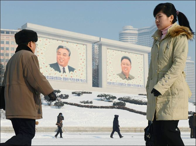 North Korea Rocket Launch North Koreans walk by the portraits of they country's national founder Kim Il Sung, left, and late leader Kim Jong Il in Pyongyang, North Korea today.
