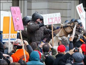 Michigan State Police  on horseback move demonstrators away from the Michigan State Capitol.