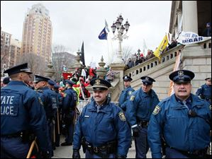Michigan State Police stand guard as demonstrators protest against right to work legislation.