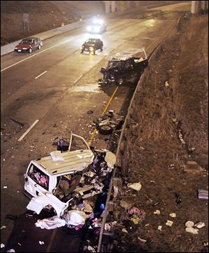 A white van carrying a family of eight from Maryland lies crumpled against a guardrail on southbound I-280 near the Manhaten Blvd. exit in Toledo, Ohio in 2007. 5 members of the Maryland family died when a dark colored pickup shown against the guardrail (center)  traveled the wrong way on the four-lane highway.