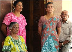 Carmine Barboza, seated left, Mother-in-law of nurse at King Edward VII hospital, in London, Jacintha Saldanha, is seen with her unidentified relatives as she speaks to the media after knowing about Saldanha's death in central London, at their village house in Shirva north of Mangalore, India.