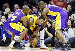 The Lakers' Kobe Bryant, left, and Antawn Jamison, right, attempt to slow Cavaliers point guard Kyrie Irving, who scored 28 points in a home victory.