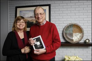 Bill and Barb McMillen pose with one of their Christmas stories that they send out as Christmas cards at their home in Perrysburg.  Bill writes the story and Barb designs the book. They print about 300 copies.
