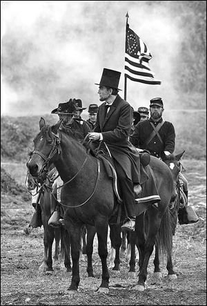 Daniel Day-Lewis, center, as President Abraham Lincoln, looks across a battlefield in the aftermath of a terrible siege in this scene from director Steven Spielberg's drama 'Lincoln.'