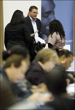 Job seekers surround Tim Taylor of Manpower Inc. of Toledo at a job fair at Seagate Convention Centre this fall. Manpower's hiring outlook for 2013 is similar to this year's.