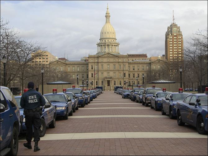 Right to Work Michigan State Police Michigan State Police cruisers line the pedestrian walkway west of the state Capitol in Lansing, Mich., Monday.