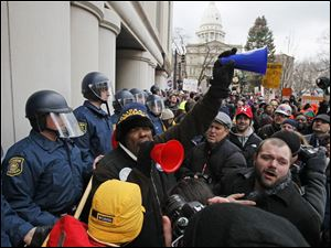 Demonstrators protest against right to work legislation outside the George W. Romney State Office Building in Lansing, Mich.