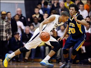 St. John's Marc Loving (32) drives past Whitmer's Chris Boykin (20).