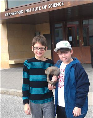 Eric Stamatin, left, and Andrew Gainariu stand outside the museum in Bloomfield Hills, Mich. Stamatin, 11, of Shelby Township, and his cousin, Andrew Gainariu, also 11, of Troy, found the mastodon bone over the summer while exploring in Eric's backyard.