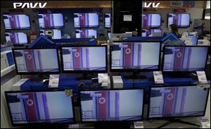 A clerk passes by TV screens, airing file footage and reporting about North Korea's rocket launch, at an electronic shop in Seoul, South Korea.