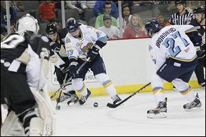 Walleye right wingman Luke Glendening, center, and left wingman Terry Broadhurst, right, fight for control of the puck during the first period against the Wheeling Nailers at the Huntington Center in Toledo.