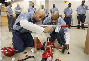 Inmates Rubin Johnson III, left, and Thomas Claybourne assemble a donated tricycle. It is one of those to be given to children who are served by Lucas County Children Services.