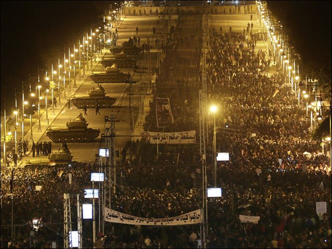 APTOPIX Mideast Egypt Egyptian Army tanks, left, deploy  as Egyptian protesters gather outside the presidential palace during a demonstration against President Mohammed Morsi in Cairo, Egypt, Tuesday.