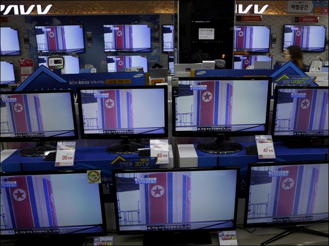 South Korea North Korea Rocket Launch A clerk passes by TV screens, airing file footage and reporting about North Korea's rocket launch, at an electronic shop in Seoul, South Korea.
