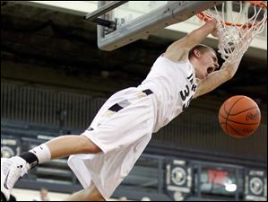 Perrysburg's Shane Edwards (35) roars as he dunks the ball against Napoleon.