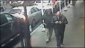 This still image made from a video provided by the New York City Police Department shows the gunman, left, behind Brandon Lincoln Woodard pulling the weapon from his jacket pocket a moment before the shooting, Mon. Dec. 10, 2012 in New York. A security camera photo shows a man pulling a weapon from his pocket moments before police say he shot a Los Angeles man in midtown Manhattan. The NYPD released the photo Tuesday amid a manhunt for the unidentified suspect in the execution-style slaying (Ap Photo/New York Police Department/ HO)