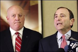 NHL Commissioner Gary Bettman, right, and deputy commissioner Bill Daly speak to reporters in New York. The NHL eliminated 16 more days from the regular-season schedule Monday.