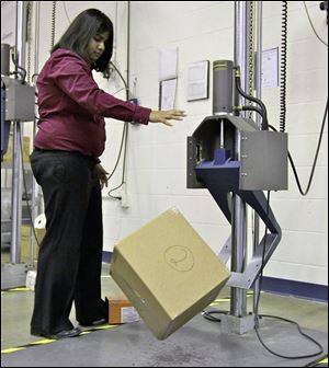 UPS packaging engineer Preeti Agrawal uses a drop impact tester that simulates a box traveling through the small parcel system at the UPS Package Design and Testing Lab in Addison, Ill. UPS tests new packaging designs by dropping, shaking, and smashing boxes.