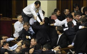 Ukrainian lawmakers fight around the rostrum during the first session of Ukraine's newly elected parliament in Kiev, Ukraine.