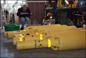 Scientific buoys that were placed on Lake Erie lie on the floor of a storage unit. The buoys are used to record temperature data of the lake. Three are missing, and the officials are asking for help to recover them.