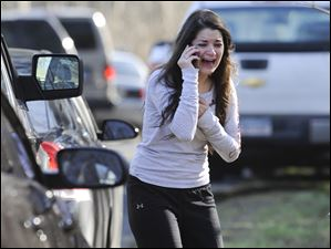 A woman waits to hear about her sister, a teacher, following a shooting at the Sandy Hook Elementary School in Newtown, Conn.