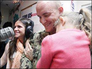 Julie Luffy, left, watches as her children are hugged by her husband Eric Luffy, right,  after a surprise homecoming on air at Star 105. Luffy came home from the UAE early for the holidays.