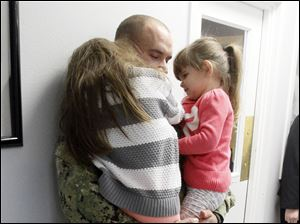 EN1 Eric Luffy, center, takes a moment in the hallway to hug daughters Aubrey Sadowy, left, and Alivia Sadowy, 4, right.