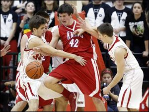 Central Catholic's Tom vetter (33) and Zach Pacer (5) defend against St. Francis' Jay Snell (42).