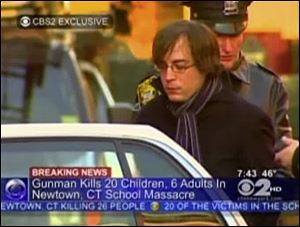 Ryan Lanza, the 24-year-old brother of Sandy Hook Elementary School shooter Adam Lanza, is escorted by police into a cruiser in Hoboken, N.J.