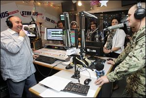 Star 105 radio host Andrew Zepeda, left,  chats with 1st Class PO Eric Luffy on the air before he surprises his family with an early holiday homecoming.
