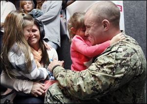 Julie Luffy, left, holds daughter Aubrey Sadowy, 6, while her husband, PO 1st Class Eric Luffy, holds daughter Alivia Luffy after their on-air surprise homecoming at the Star 105 studio in Toledo. Mr. Luffy just returned from seven months' duty in the United Arab Emirates.