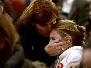 A woman comforts a young girl during a vigil service for victims of the Sandy Hook Elementary shooting.