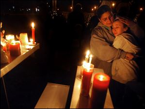 Brenda Hernadez of Enfield Conn., comforts her daughter Crystal at a makeshift shrine on the Enfield Town Green, Friday evening.