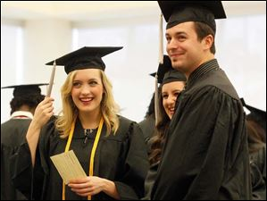 Grads Kara Bergman, left, from Dayton, Rachel Beck, center, from Brighton, Michigan, and Jason Baker, right, from New Bremen, stand in the Schmidthorst Pavilion getting ready to line up for commencement.