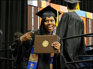 Tanecia Wilson flashes a sorority sign after receiving her diploma.