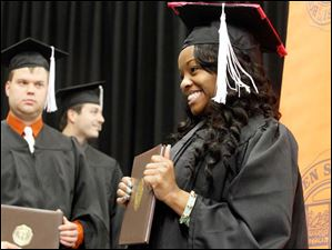 Toni Bowles smiles and holds her diploma.