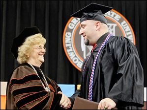 President Mary Ellen Mazey congratulates William Kilpatrick, who is wearing a special cord to distinguish him as having served in the Army from 1993 to 2003.