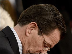 Connecticut Gov. Dannel Malloy bows his head during a moment of silence during a vigil service for victims of the Sandy Hook Elementary School shooting, at the St. Rose of Lima Roman Catholic Church in Newtown, Conn.