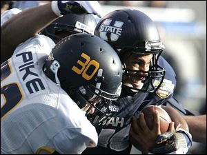 Utah State's Chuck Jacobs runs against the defense of Toledo's Ben Pike.